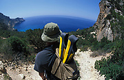 Man walking along cliff top, carrying backpack with flippers, looking out at sea view, Ibiza, 2000's.