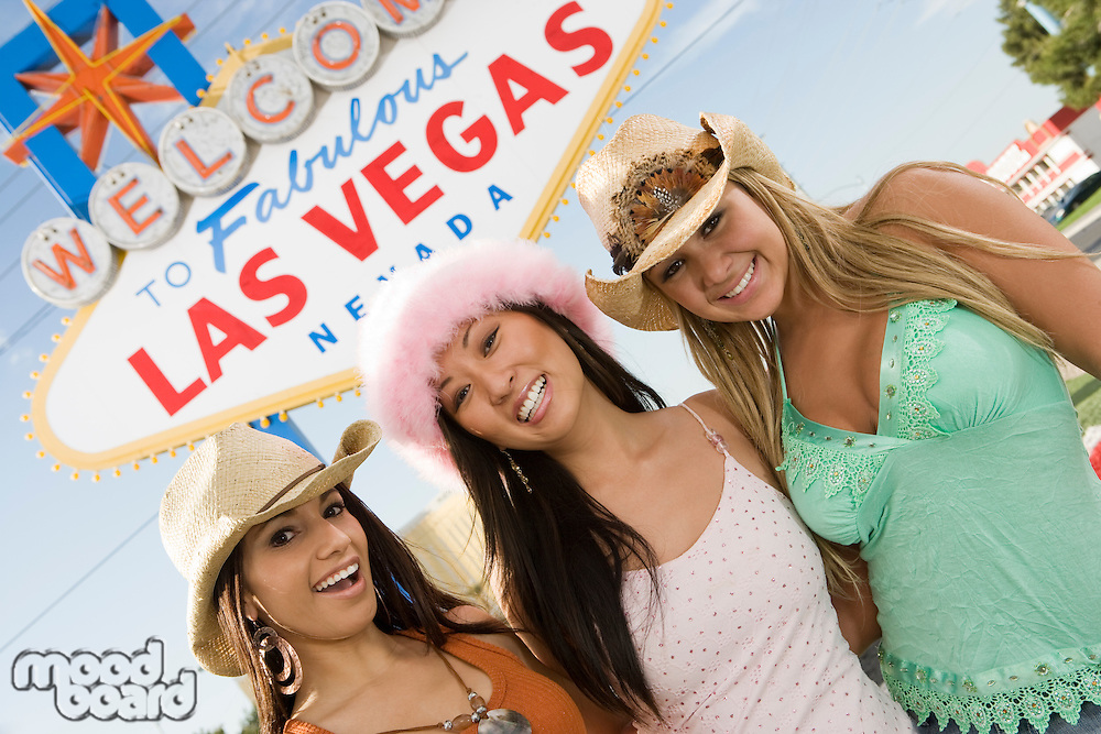 Portrait of women in front of Las Vegas welcome sign, Nevada, USA