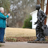 Adam Robison | BUY AT PHOTOS.DJOURNAL.COM<br /> Mary Pye, of England, takes a picture of the bronze statue of Elvis at the age of 13, Friday afternoon at the Birthplace in Tupelo.