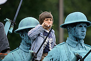 Canadian child eating ice lolly while watching parade from vantage point on Charlottetown war memorial, Canada