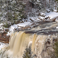 Framed by snow-covered trees, icy Blackwater Falls runs fast during a snow melt. Blackwater Falls State Park, WV.