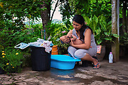 A Thai woman gives her newborn a bath in a small tub by the water spicket. PHOTO BY LEE CRAKER