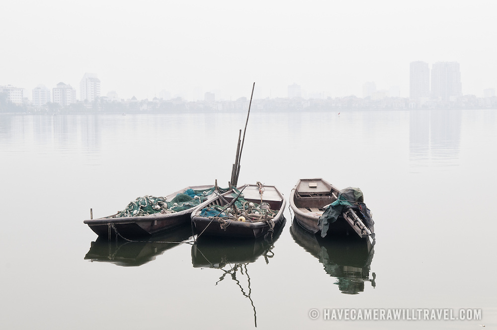 Three wooden sampans moored on West Lake (Ho Tay) in Hanoi, Vietnam. The heavy haze mostly obscures the far shore.