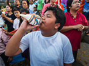 20 SEPTEMBER 2015 - SARIKA, NAKHON NAYOK, THAILAND: A boy blows a conch shell at the Ganesh festival at Shri Utthayan Ganesha Temple in Sarika, Nakhon Nayok. Ganesh Chaturthi, also known as Vinayaka Chaturthi, is a Hindu festival dedicated to Lord Ganesh. Ganesh is the patron of arts and sciences, the deity of intellect and wisdom -- identified by his elephant head. The holiday is celebrated for 10 days. Wat Utthaya Ganesh in Nakhon Nayok province, is a Buddhist temple that venerates Ganesh, who is popular with Thai Buddhists. The temple draws both Buddhists and Hindus and celebrates the Ganesh holiday a week ahead of most other places.    PHOTO BY JACK KURTZ