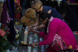 London, June 15th 2017. Local residents and well-wishers gather at a short vigil outside Notting Hill Methodist Church near the scene of the Grenfell Tower Fire Disaster in which so far seventeen people have been reported killed, with dozens injured, many still missing and scores of people rendered homeless. PICTURED: Women light candles outside the church.