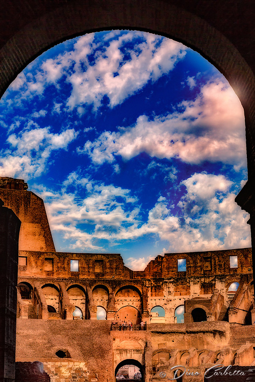 &quot;Dramatic clouds gather through the Arch of the Colosseum&quot;...<br /> <br /> A sunlit and pleasant view peering into the ancient and organic Colosseum. The Colosseum, is an elliptical amphitheatre in the center of the city of Rome, the largest ever built during the Roman Empire. One of the greatest works of Roman architecture and engineering in history, its construction started in 72 AD under the emperor Vespasian and was completed in 80 AD under Titus. Capable of seating 65,000 spectators, it was used for gladiatorial contests and public spectacles such as mock sea battles, animal hunts, executions, re-enactments of famous battles, and dramas based on Classical mythology. The building ceased to be used for entertainment in the early medieval era. It is one of Rome's most popular tourist attractions and still has close connections with the Roman Catholic Church, as each Good Friday the Pope leads a torch lit &quot;Way of the Cross&quot; procession that starts in the area around the Colosseum. The Colosseum is generally regarded by Christians as a site of the martyrdom of large numbers of believers during the persecution of Christians in the Roman Empire, as evidenced by Church history and tradition. A Cross stands exultant in the Colosseum center with a plaque stating: &ldquo;The amphitheatre, one consecrated to triumphs, entertainments, and the impious worship of pagan gods, is now dedicated to the sufferings of the martyrs purified from impious superstitions.&rdquo; In viewing many historical sites during my journey in Italy, seeing the iconic Colosseum for the first time&hellip;I became awestruck. It is as grand in person as it appears in the media, and it seems to hold a very mystical aura. Climbing the ancient steps inside, one cannot help but feel not only the suffering of its past, but the forgiveness and sacrifice of its present stature.