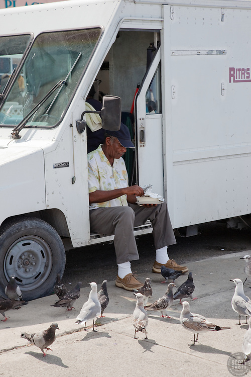 Man feeding pigeons from a food truck in Nassau, Bahamas.