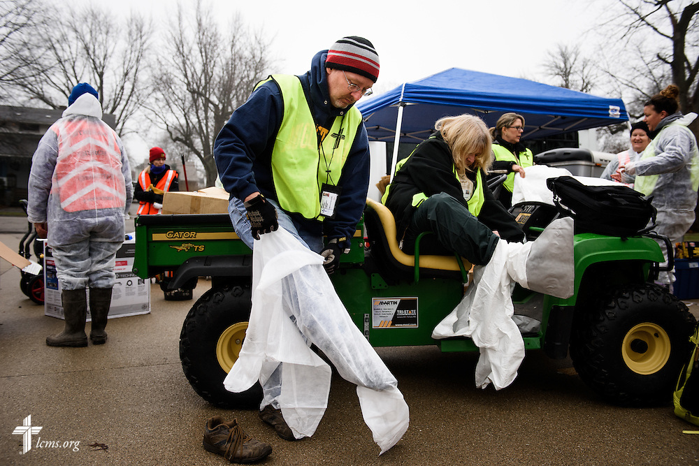 Brent Amidon of Mount Pulaski, Ill., dons protective clothing during a volunteer event for cleanup of flood-damaged homes on Saturday, Jan. 9, 2016, in Watseka, Ill. LCMS Communications/Erik M. Lunsford