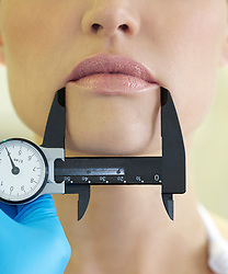 Doctor's Hand Holding Calipers Measuring Woman's Mouth - Close up view