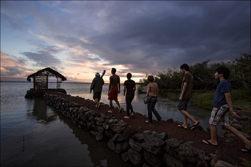 """Like the Pied Piper, Brother Nolan also referred to as """"Uncle No"""" leads his charges out for a little sunset kanikapila at the Ho'ea Initiative base camp located at the Keawanui Fishpond on Molokai."""