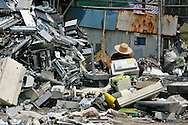 A worker processes electronic trash in an area where much of the world's e-waste _ from cell phone chargers to mainframe computers _ ends up in Nanyang, Guiyu and other small towns like it in eastern China, Thursday March 16, 2006. Workers, many of them poorly paid migrants strip, smash and melt down circuit boards, mainly to extract the copper and other precious metals inside.The business has created massive pollution from leaded glass and other toxic materials. Such pollution could be mitigated by moves to recycle and properly dispose of so-called electronic waste that are gaining ground in the West.