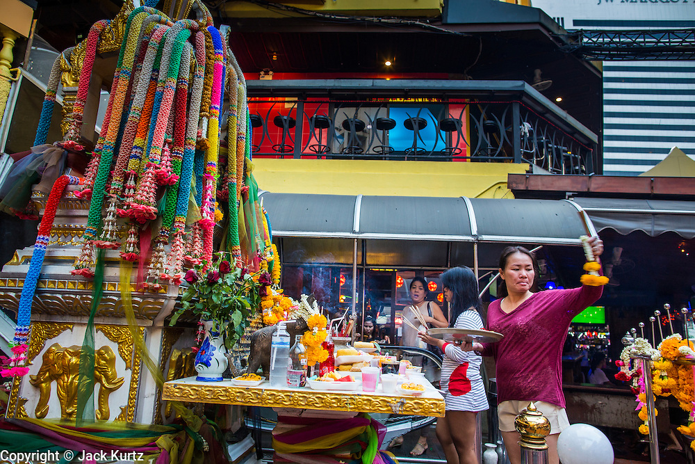 "21 JANUARY 2013 - BANGKOK, THAILAND:  Workers in the Nana Entertainment Plaza, a red light district in Bangkok, pray and make offerings at a shrine at the entrance to the plaza. Prostitution in Thailand is technically illegal, although in practice it is tolerated and partly regulated. Prostitution is practiced openly throughout the country. The number of prostitutes is difficult to determine, estimates vary widely. Since the Vietnam War, Thailand has gained international notoriety among travelers from many countries as a sex tourism destination. One estimate published in 2003 placed the trade at US$ 4.3 billion per year or about three percent of the Thai economy. It has been suggested that at least 10% of tourist dollars may be spent on the sex trade. According to a 2001 report by the World Health Organisation: ""There are between 150,000 and 200,000 sex workers (in Thailand).""  PHOTO BY JACK KURTZ"