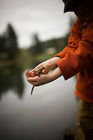 A boy holds a wet slippery salamander at a lake near Portland, Oregon.