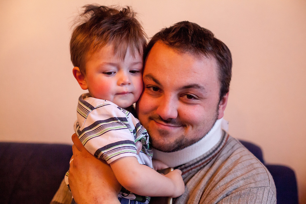 Former refugee Elvis Causevic with his son Aldin (1 1/2) in the living room at the  families house in Hadžići. The family settled here after the war ended in Bosnia. Hadžići is a town and a municipality located about 20 km south west of Sarajevo city but within the Sarajevo Canton of Bosnia and Herzegovina. According to the census of 2013, Hadžići municipality has a population of 23,891 residents.