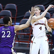 David Walker #4 of the Northeastern Huskies passes the ball past Taylor Bessick #22 of the James Madison University Dukes during the game at Matthews Arena on January 29, 2014 in Boston, Massachusetts . (Photo by Elan Kawesch)