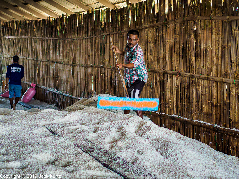 20 FEBRUARY 2019 - BAN LAEM, PHETCHABURI, THAILAND: A salt worker rakes salt in the warehouse on one of the first days of the 2019 salt harvest in Ban Laem, Thailand. Ban Laem's salt fields are expanding because salt harvesters in Samut Sakhon and Samut Songkhram,  which are closer to Bangkok, are moving to Ban Laem as their land is turned into industrial parks.     PHOTO BY JACK KURTZ
