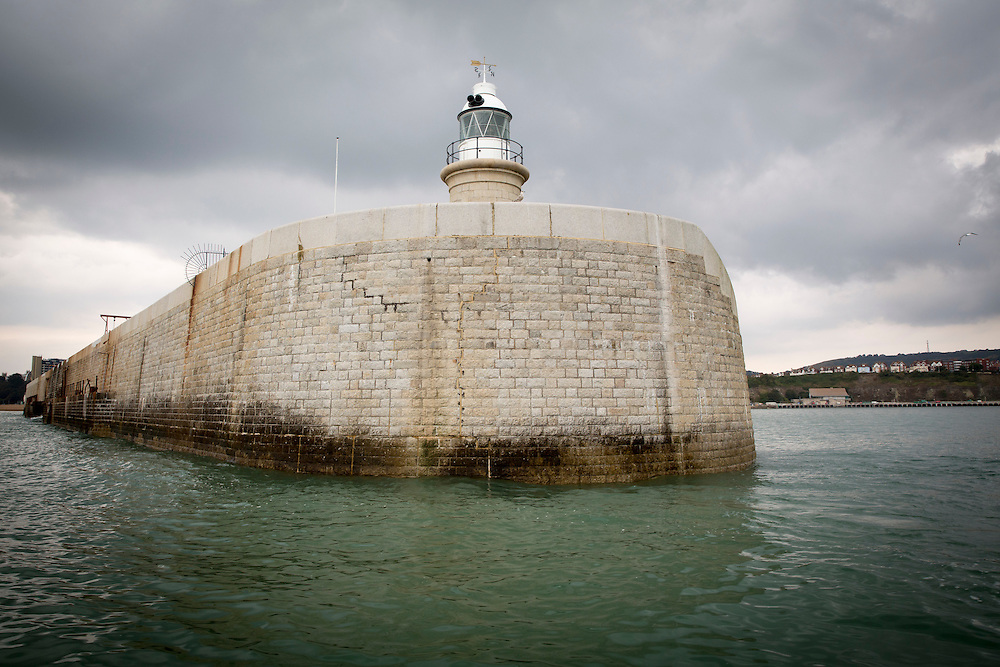 The lighthouse at the end of Folkestone Harbour Arm pier with Folkestone town in the background, on a cloudy day photographed from a boat in The English Channel off Folkestone seafront, Kent, England, United Kingdom. <br /> (photo by Andrew Aitchison / In pictures via Getty Images)