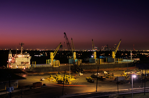 Night view of cranes working on a tanker in the Port of Houston
