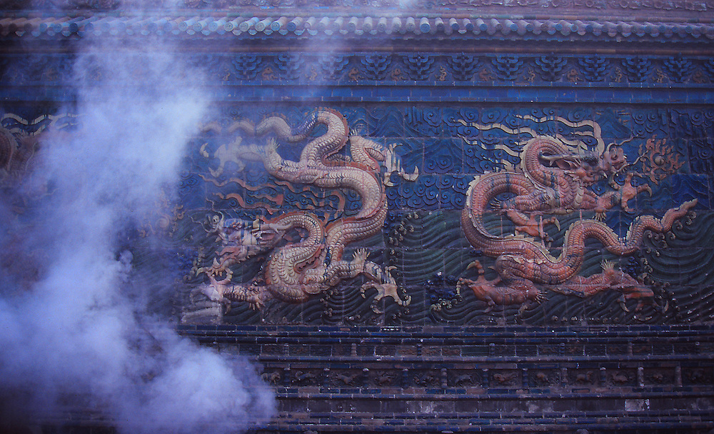 Dragons fighting against incense volutes on a Datong's ceramic wall, China.