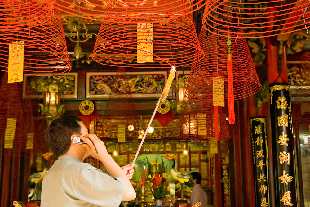 Man talking on a mobile telephone while he lights incense spiral cones at a Vietnamese pagoda, Phong Thuong Truc, near the Marble Mountain, North Vietnam.