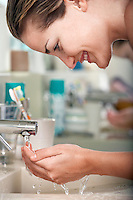 Woman washing face in bathroom close-up