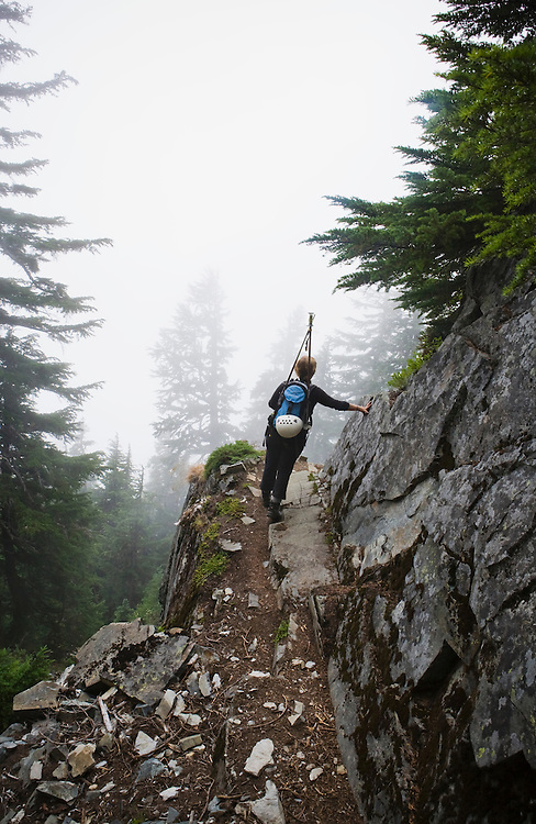 A young woman walking out on a cliff ledge overlooking a mist filled valley, Washington Cascades, USA.