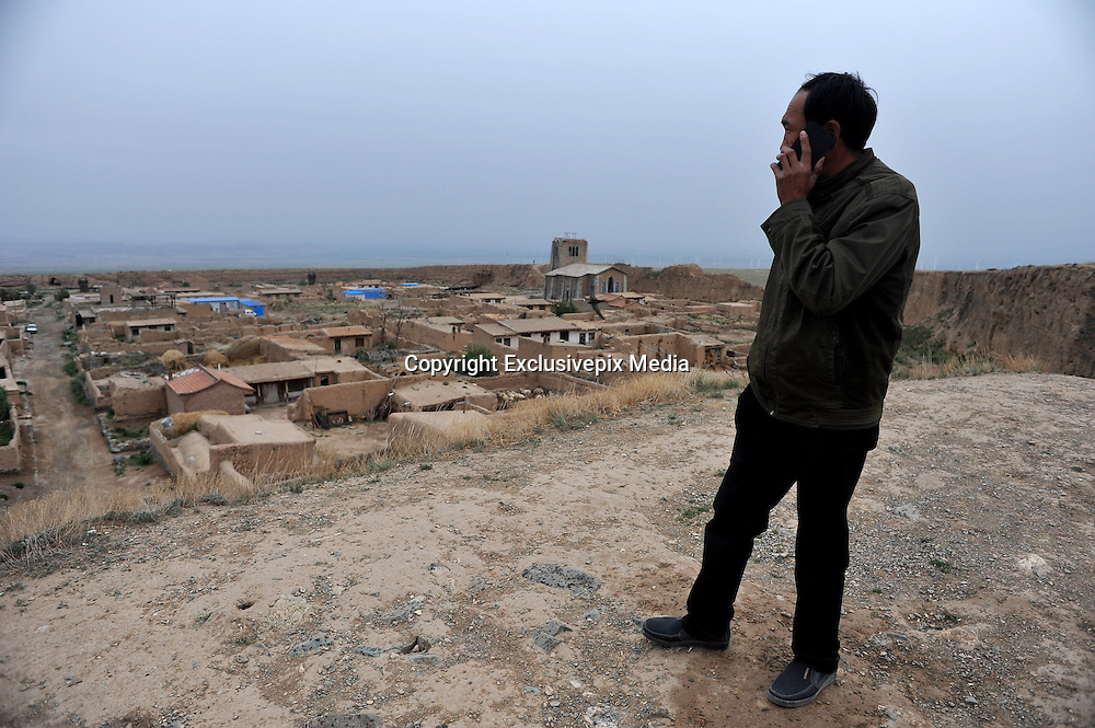 JINGTAI, CHINA - JUNE 20: (CHINA OUT) <br /> <br /> City inside 12 meter high walls<br /> <br /> A man makes a phone call on the city wall of the Yongtai Acient City on June 19, 2015 in Jingtai County, Gansu Province of China. The Yongtai Ancient City, also known as the Turtle city, was built in 1608 during the Ming Dynasty (1368-1644). With a perimeter of 1,717 meters, the city wall is 12 meters in height. The city also has a six-meter wide and one-to-2.5-meter deep moat. In 2006, the city was listed as the sixth batch of nation key cultural relic preservation organ. There are more than 100 villagers still living in the city.<br /> ©Exclusivepix Media