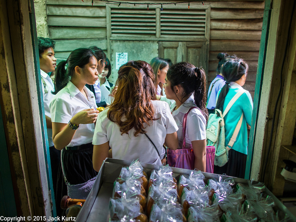 "06 FEBRUARY 2015 - BANGKOK, THAILAND: University students buy fresh baked cakes at the walkup window at Thanusingha Bakery, a bakery that specializes in traditional Thai Catholic desert cakes. The cakes are called ""Kanom Farang Kudeejeen"" or ""Chinese Monk Candy."" The tradition of baking the cakes, about the size of a cupcake or muffin, started in Siam (now Thailand) in the 17th century AD when Portuguese Catholic priests accompanied Portuguese soldiers who assisted the Siamese in their wars with Burma. Several hundred Siamese (Thai) Buddhists converted to Catholicism and started baking the cakes. When the Siamese Empire in Ayutthaya was sacked by the Burmese the Portuguese and Thai Catholics fled to Thonburi, in what is now Bangkok. The Portuguese established a Catholic church near the new Siamese capital. Now just three families bake the cakes, using a recipe that is 400 years old and contains eggs, wheat flour, sugar, water and raisins. The same family has been baking the cakes at the Thanusingha Bakery, near Santa Cruz Church, for more than five generations. There are still a large number of Thai Catholics living in the neighborhood around the church.        PHOTO BY JACK KURTZ"