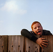 Young boy climbing on fence, High Wycombe, UK, 1980s.
