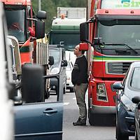 Nederland Rotterdam 30-09-2010 20100930..File op de rijksweg A16 op de oosterlijke ring, lange rijen met auto's staan stil. Man vrachtwagen chauffeur is uit vrachtwagen gestapt en maakt een praatje met collega, mensen,  Traffic jam. Holland, The Netherlands, dutch, Pays Bas, Europe , ,traffic,.,truck,.trucks,..,verkeer,..vrachtauto,.vrachtauto's,.vrachtwagen,.vrachtwagens,..,vrachtauto,vrachtauto's,vrachtverkeer,vrachtvervoer,vrachtvervoerders,vrachtwagen,vrachtwagenchauffeur,vrachtwagenchauffeurs,vrachtwagens,.,vervoerssector,..,vervoer,vervoerder,..,transport,transport over de weg,transport sector,transportation,transportbedrijf,transportbedrijven,transportbranche,transportcapaciteit,transporteren,transporteur,transporteurs,transportnet,transportondernemers,transportonderneming,transportsector,transportwerktuigen,truck,trucker,truckers,trucks,..,rij tijd,rij tijden,rijtijden,rijtijdenwet,..Foto: David Rozing