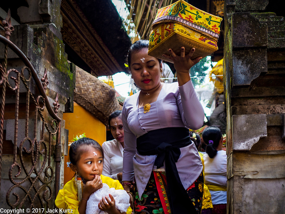 """02 AUGUST 2017 - UBUD, BALI, INDONESIA: People leave the temple after making an offering during the """"Merchants' Day"""" ceremony at the Pura (Temple) Melanting Pasar Ubud, the small Hindu temple in the Ubud market. It's a day that merchants throughout Ubud come to the temple to make offerings and pray for prosperity.    PHOTO BY JACK KURTZ"""
