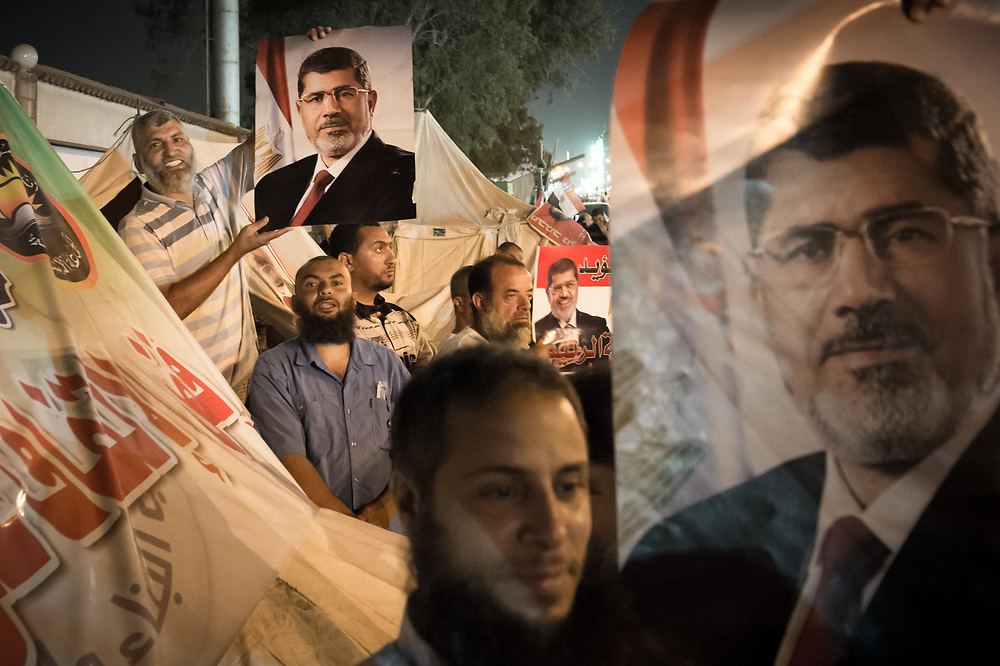 Supporters of ousted president Morsi showing posters with the face of Morsi during a sit-in on Rabaa Al-Adawiya Square in Cairo, Egypt, July 5, 2013