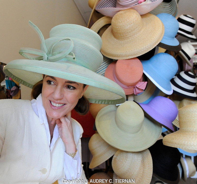 "BRIDGEHAMPTON, NY: Tuesday, March 31, 2009--- Anne Moore, a miliner poses in her shop amid the hats she designed and wears ""Confection"" made from green horsehair with grosgrain ribbon. © Audrey C. Tiernan"