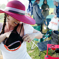 "An infielder unravels the felxible straw of her ""wine rack"", a bra storing her vodka, at her tent in the infield before the 136th running of the Kentucky Derby at Churchill Downs Saturday May 1, 2010. Photo by David Stephenson"