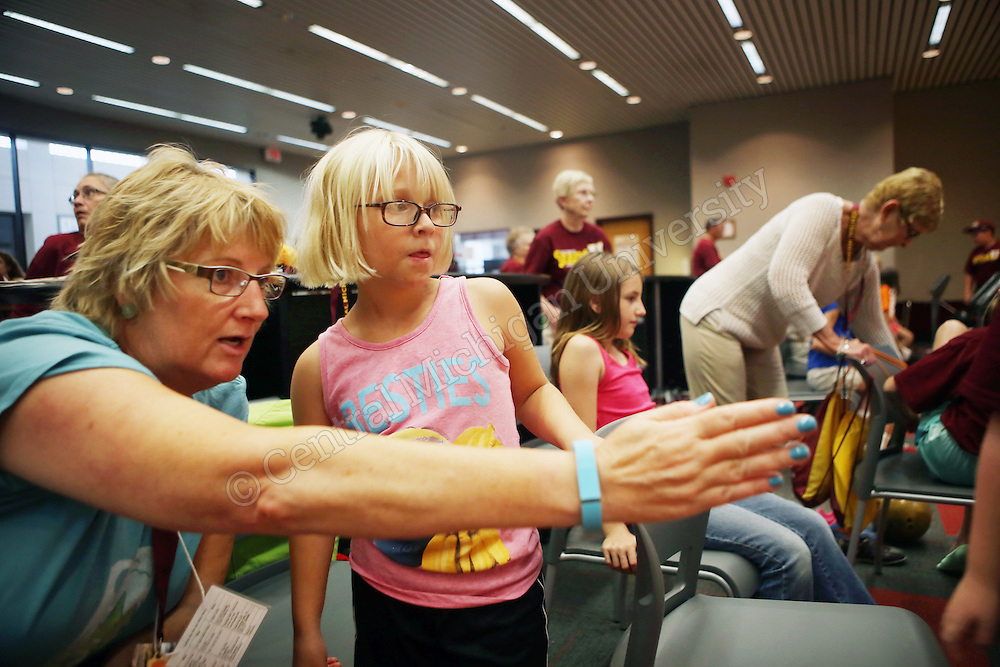 Audrey Van Alst helps 8-year-old Taylor McMath during bowling at the Student Activity Center photo by Emily Mesner
