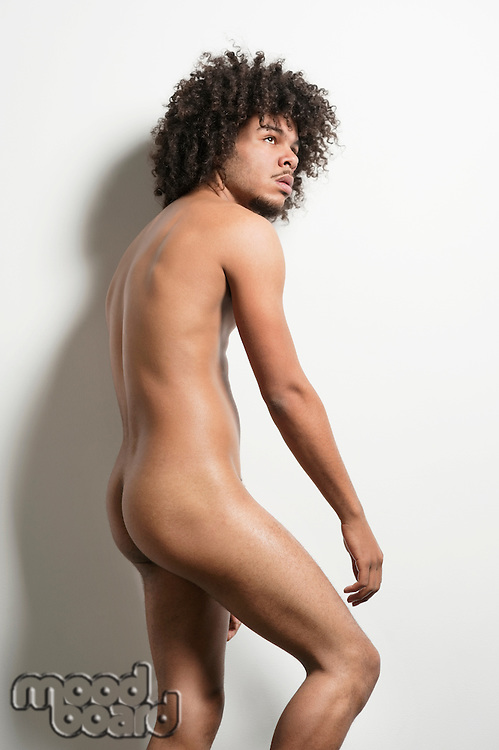 Naked young man with curly hair looking away over white background