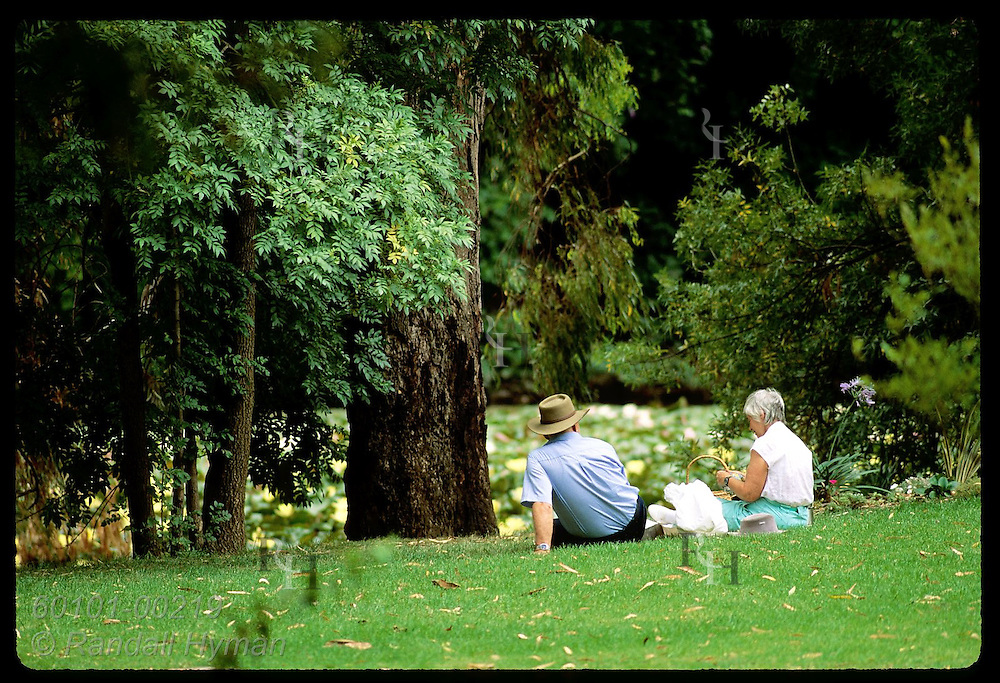 Older couple enjoys picnic lunch on bank of lagoon in public park in Wagga Wagga, NSW. Australia