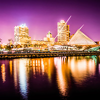 Milwaukee skyline at night picture in purple. Photo includes the Milwaukee lakefront, Milwaukee Art Museum, University Club Tower, and Northwestern Mutual Tower. Photo is high resolution.