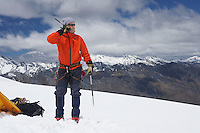 Hiker using walkie-talkie on snowy mountain peak
