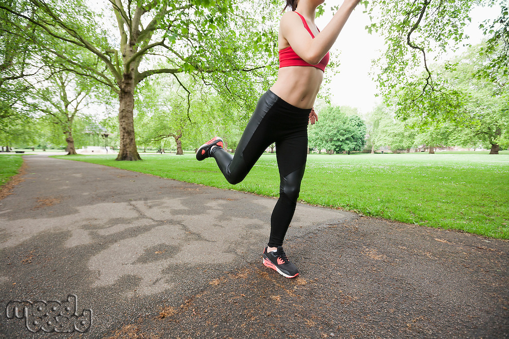 Low section of young woman jogging in park