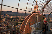 Tourists stand opposite Brunelleschi's Dome on Giotto's Bell Tower (campanile) in Florence..They have climbed 414 steps up 84.7 meters (277.9 ft) high Gioto's Belltower (or campanile) of Duomo Cathedral. .The Basilica di Santa Maria del Fiore is the cathedral church (Duomo) of Florence, Italy, begun in 1296 in the Gothic style to the design of Arnolfo di Cambio and completed structurally in 1436 with the dome engineered by Filippo Brunelleschi. The exterior of the basilica is faced with polychrome marble panels in various shades of green and pink bordered by white and has an elaborate 19th century Gothic Revival facade by Emilio De Fabris. The cathedral complex, located in Piazza del Duomo, includes the Baptistery and Giotto's Campanile. The three buildings are part of the UNESCO World Heritage Site .