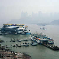 Ferry passengers disembarking from a ferry across the Yangtze River, with downtown highrise buildings behind appearing through typical Chongqing pollution haze.<br /> <br /> From China [sur]real &not;&copy; Mark Henley