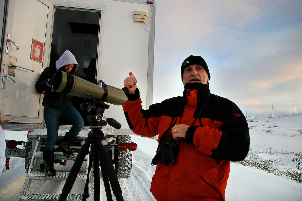 Researcher Henning Thing motions after setting up a telescope to view musk oxen near Kangerlussauq, Greenland.