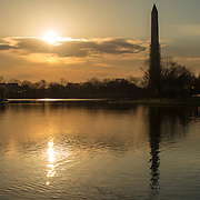 Early morning sun over the lake at Constitution Gardens on the western end of the National Mall, with the scaffolding part way up the Washington Monument as it undergoes repairs.