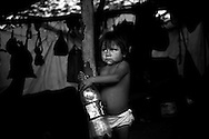A Warao girl drinks Pepsi in the camp where she lives under a plastic tarp supported by tree branches, with other Warao indigenous persons, on the outskirts of the Cambalache garbage dump in Ciudad Guayana, in northeastern Venezuela. In an effort to escape poverty, hunger and to be closer to health care facilities, approximately 300 Warao indigenous persons from the Delta Amacuro have settled in Ciudad Guayana. The Warao sustain themselves and their families by salvaging recyclables, clothing and discarded food in Cambalache. Although Warao community leaders say their quality of life is improved in comparison to the conditions in the Delta, the Warao are still plagued by hunger and diseases consequential of the unsanitary conditions of living and working in Cambalache.