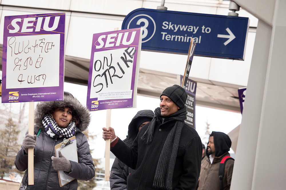 Firehiwot Bezabih, left, and Shemsedin Salih walk with signs as Twin Cities janitors represented by Service Employees International Union picket for a wage increase at Minneapolis-St. Paul International Airport's Terminal 1 February 17, 2016.  The union is asking for $15 for both full and part-time workers.