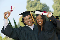 Two graduates hoisting diplomas outside portrait