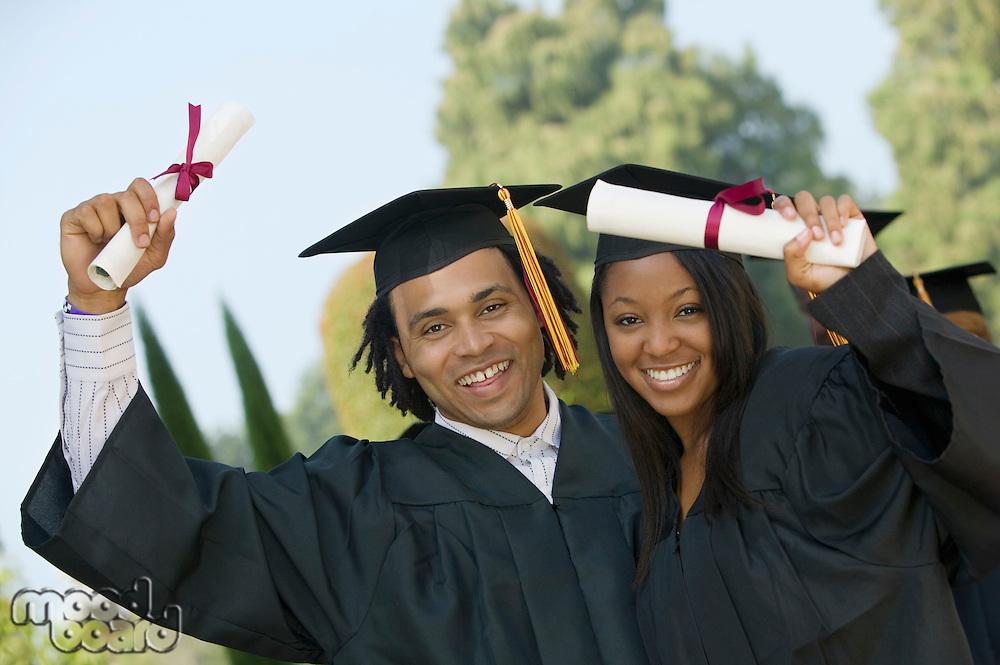 Two graduates hoisting diplomas outside portrait