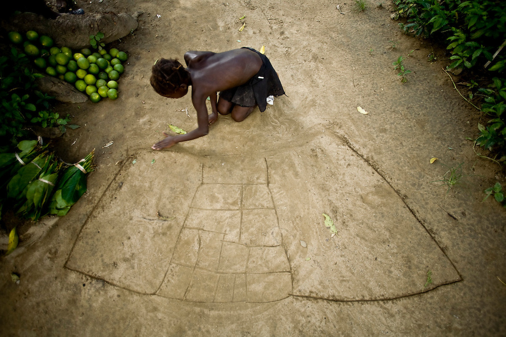 The grandchild of a Chemen Lavi Miyò  client draws a house plan in the dirt. Twoudino, Haiti. Photo by Ben Depp. 9/24/2008.