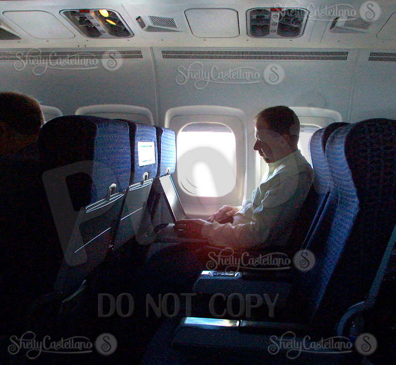 Jun 21, 2002; Dallas, TX, USA; Delta Airlines passenger works on his laptop shortly after take off in route from Dallas to Orange County in an uncrowded MD-70 plane to CA.  Mandatory Credit: Photo by Shelly Castellano/ZUMA Press. (©) Copyright 2002 by Shelly Castellano